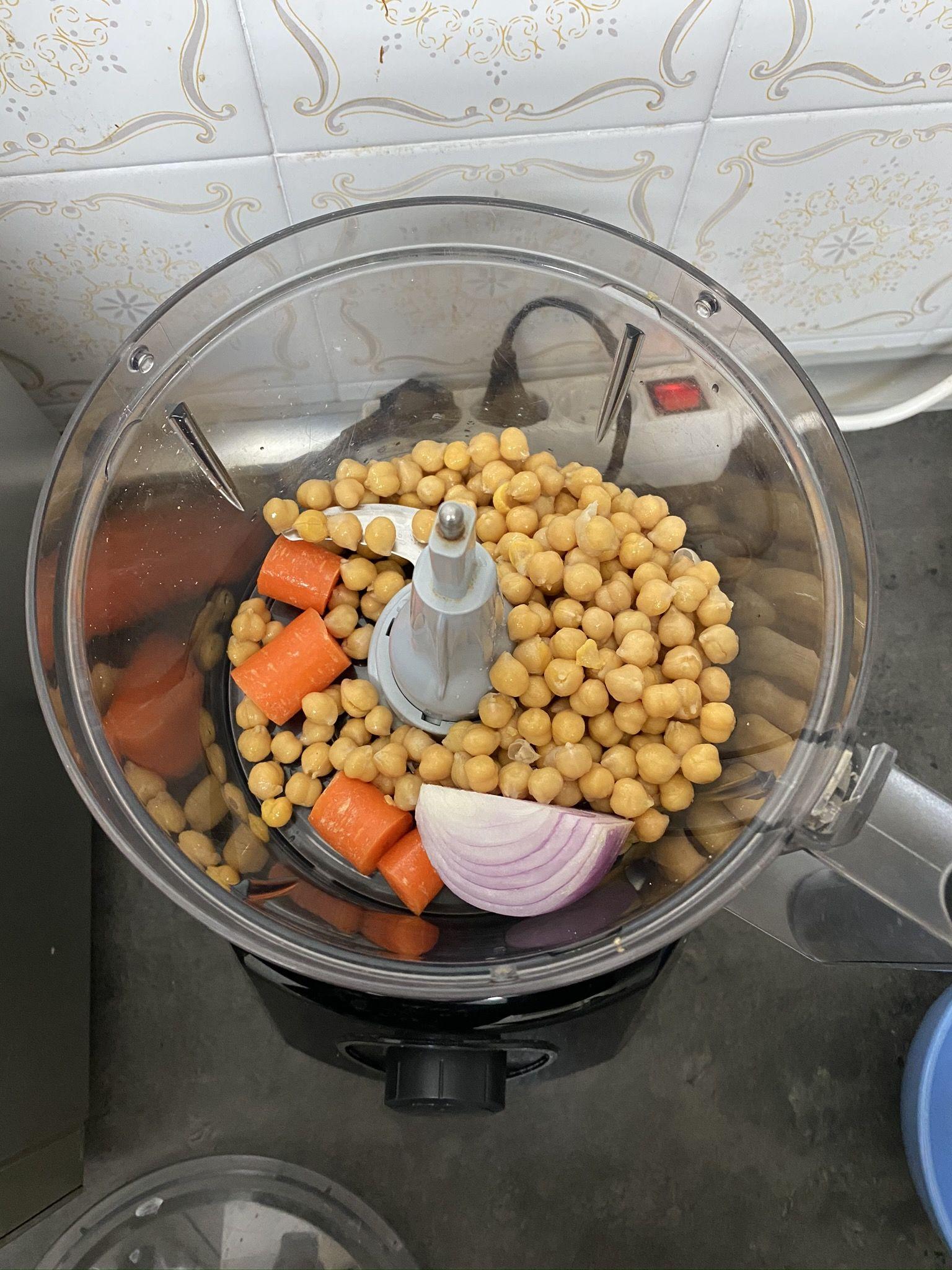 Coloca los garbanzos, la cebolla y la zanahoria en el procesador.